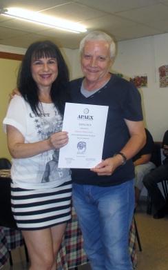 Voluntaria junto a un usuario y su diploma.